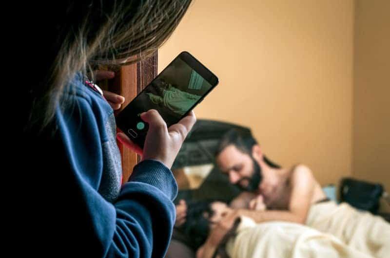 ein Mädchen, das mit seinem Handy ein Foto von einem Mann im Bett macht