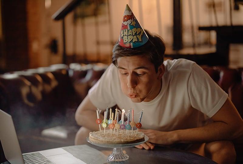 Ein Mann bläst Kerzen auf eine Geburtstagstorte, während er auf der Couch sitzt