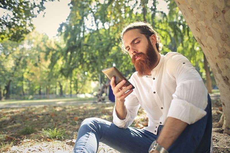 Ein Mann, der auf einem Smartphone tippt, während er alleine im Gras im Park sitzt