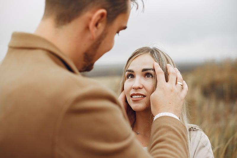 Ein Mann berührt die Haare einer Frau, während er einer Frau gegenübersteht