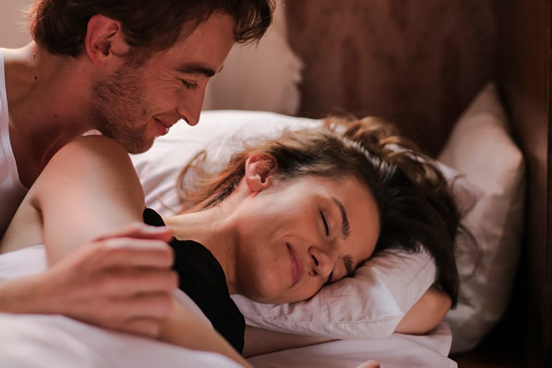 ein Mann, der eine Frau ansieht, während beide in einem Bett liegen