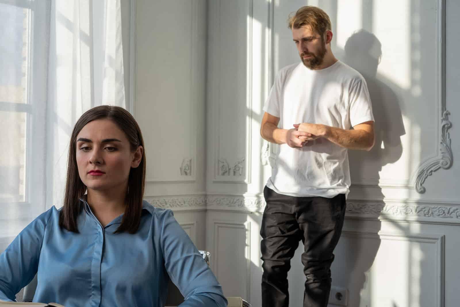 Ein Mann steht hinter einer ernsten Frau, die auf dem Stuhl sitzt