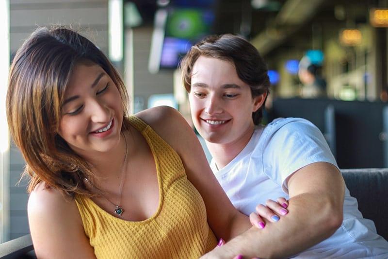 ein Mann, der versucht, ein lächelndes Mädchen in einem Café zu umarmen