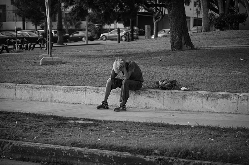 Ein Mann sitzt auf der Betonwand und hält sich die Hände auf dem Kopf