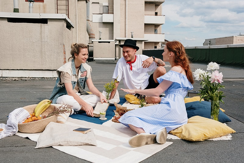 Ein Mann sitzt mit zwei Freundinnen auf der weißen Matte und spricht mit ihnen