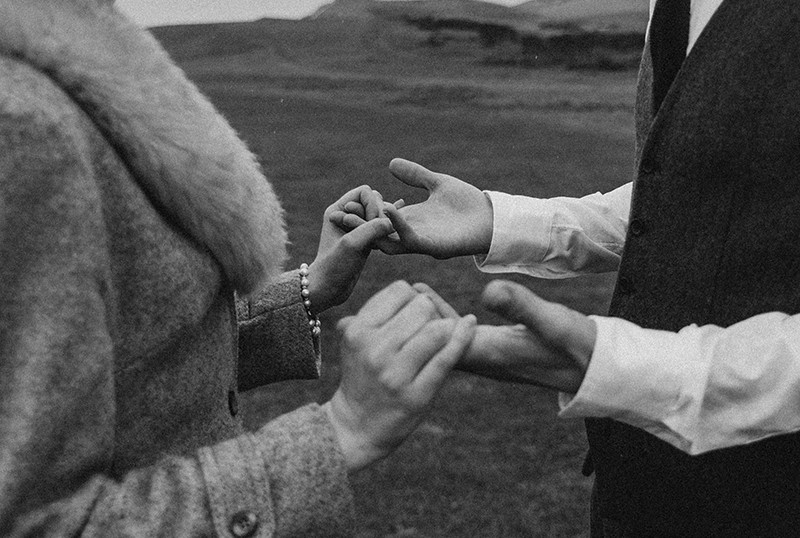 ein Mann und eine Frau, die Hände halten, während sie auf dem Gras stehen
