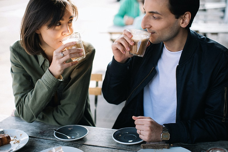 Ein Mann und eine Frau bei einem Date, die im Café Tee trinken
