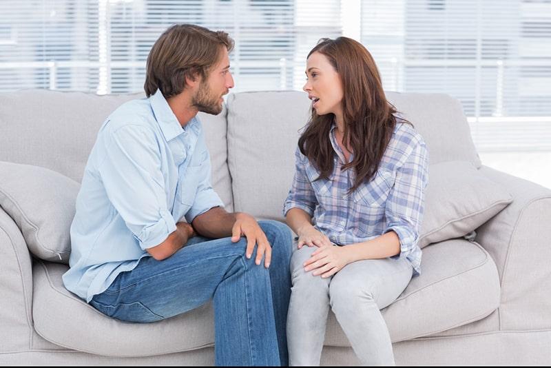 Ein Mann und eine Frau streiten sich, während sie auf der Couch sitzen