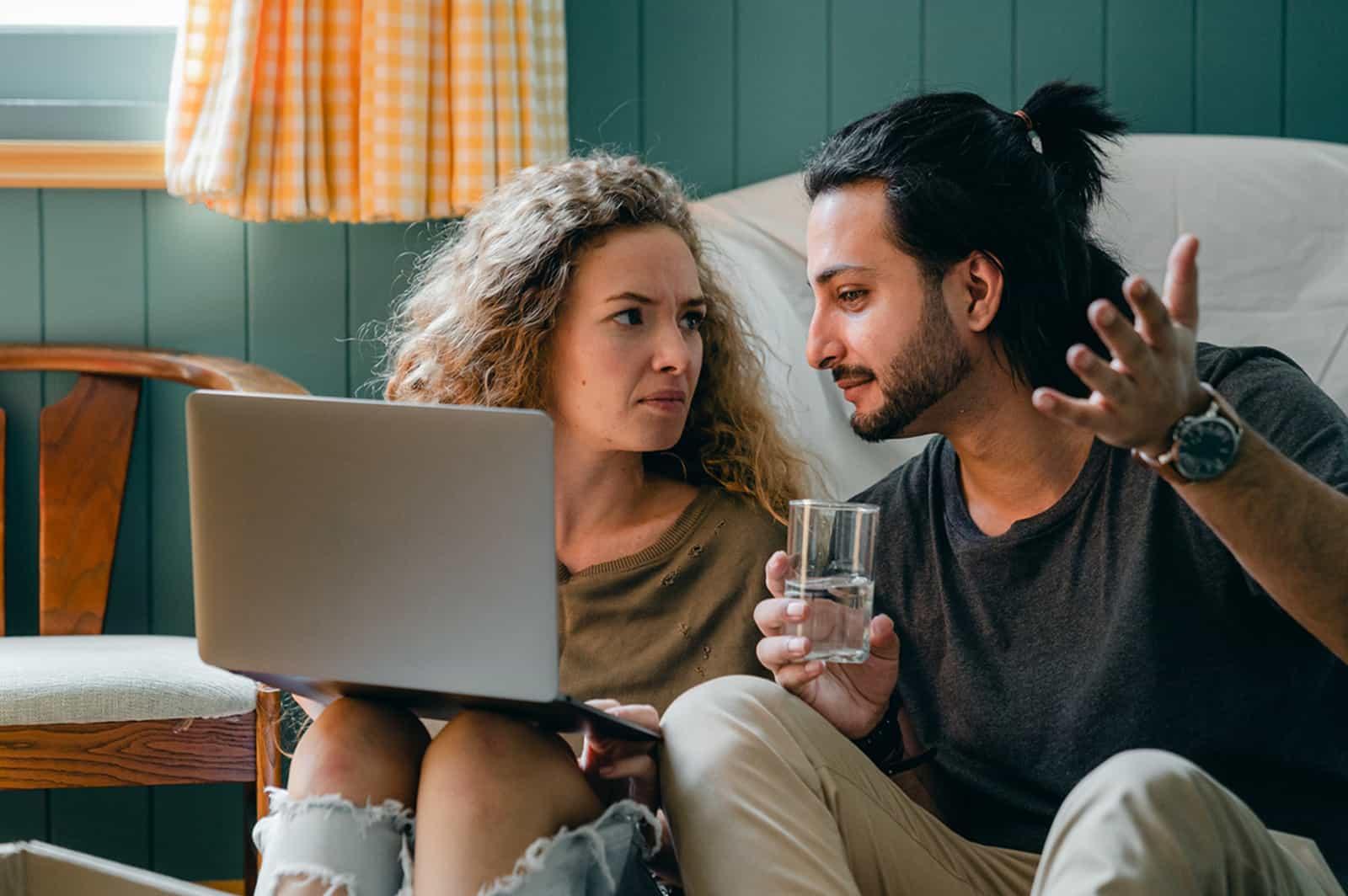 Ein Mann und eine Frau unterhalten sich, während die Frau einen Laptop auf den Knien hält