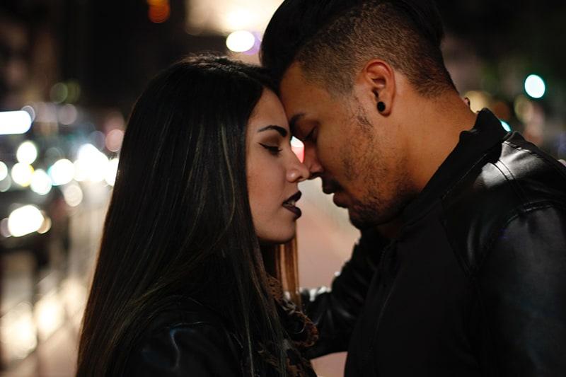 ein Paar, das sich gerade küssen will, während es abends in der Stadt steht