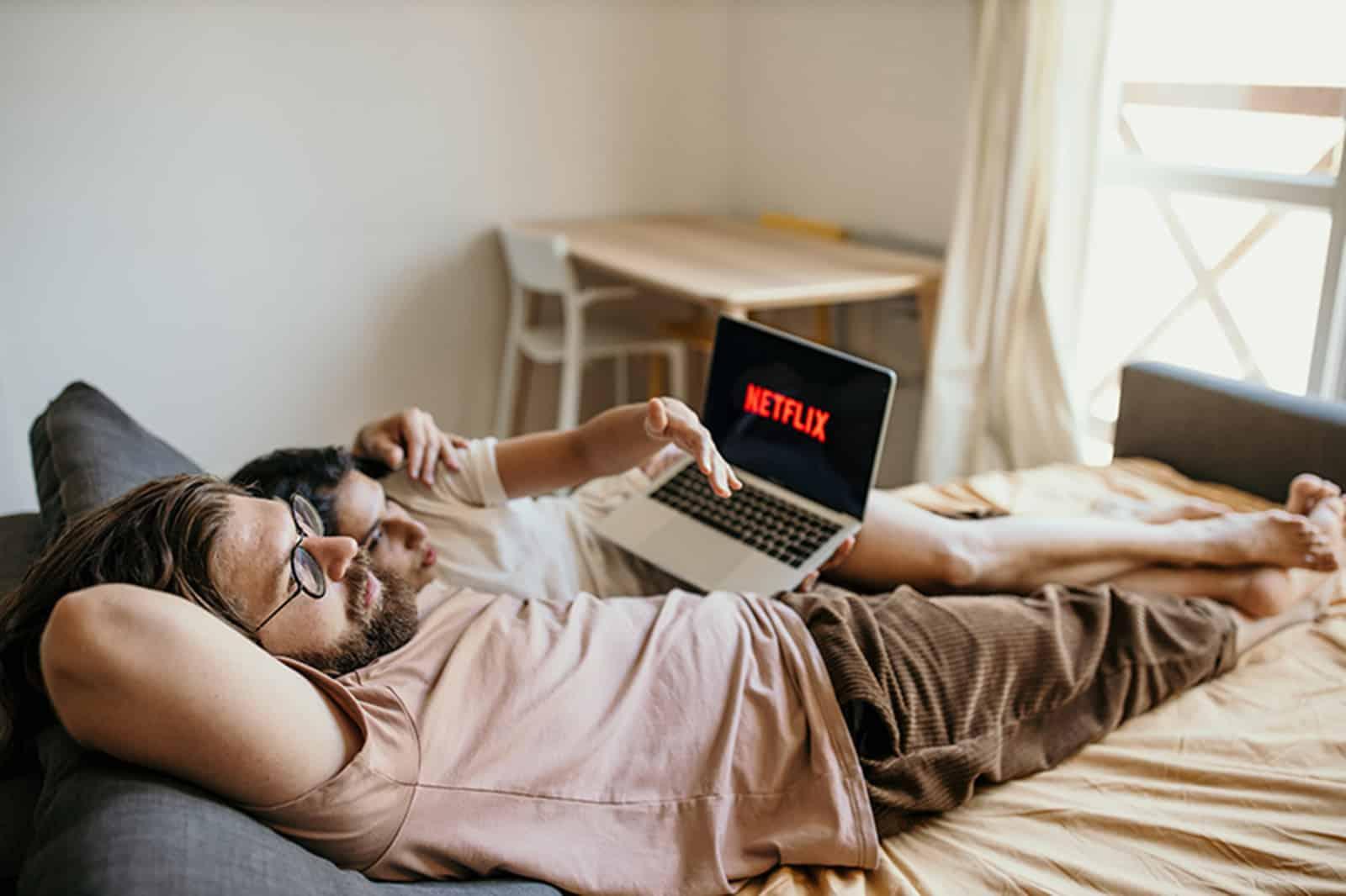 ein Paar, das in einem Bett liegt und Netflix auf einem Laptop beobachtet