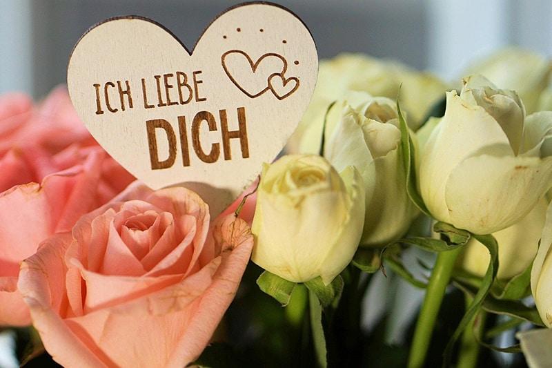 ein Strauß Rosen mit Ich liebe dich eine Nachricht auf einem Holzherz