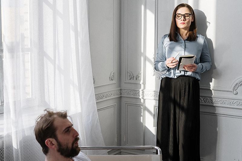 ein Therapeut, der Notizbuch und Bleistift hält, während er den Klienten ansieht