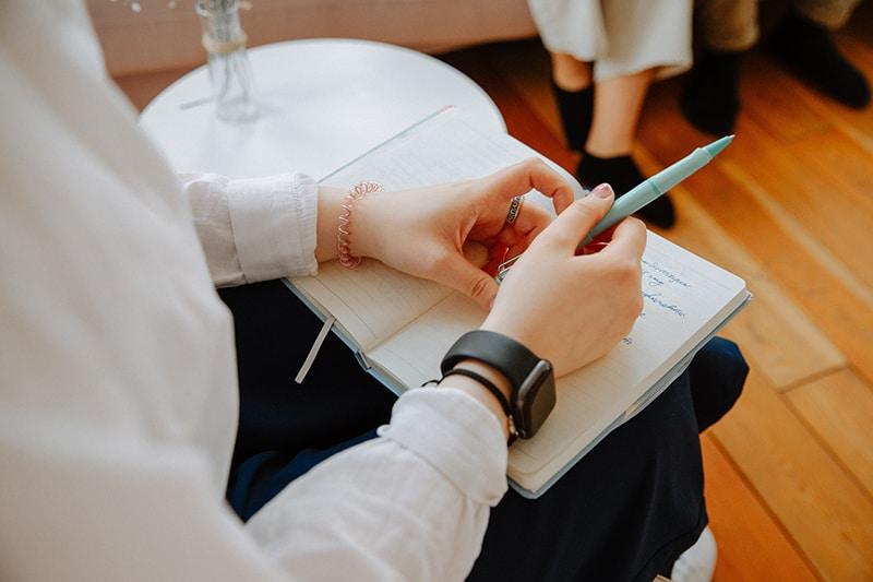 Ein Therapeut hält ein Notizbuch auf den Knien, während er auf dem Stuhl sitzt