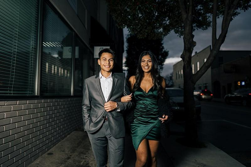 ein elegant gekleidetes Paar, das beim Gehen auf dem Bürgersteig Händchen hält