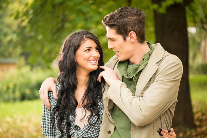 Ein glückliches Paar, das im Park spazieren geht und sich unterhält