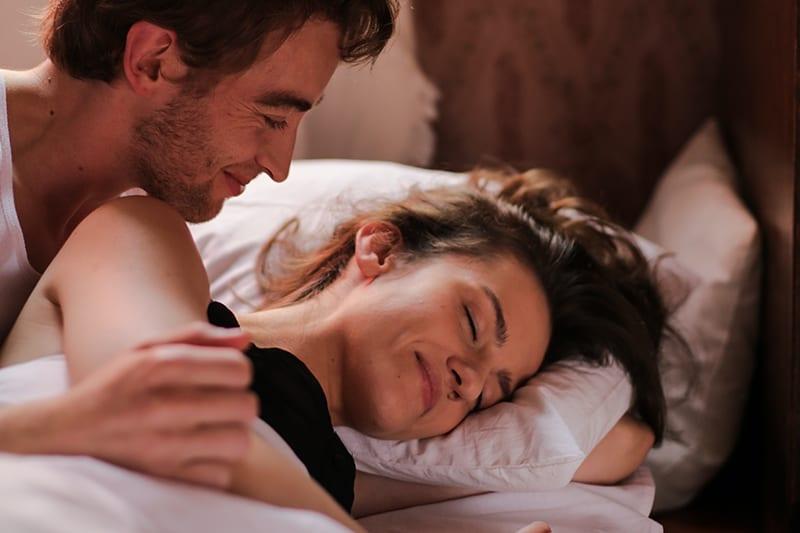 ein lächelnder Mann, der seine schlafende Freundin im Bett ansieht