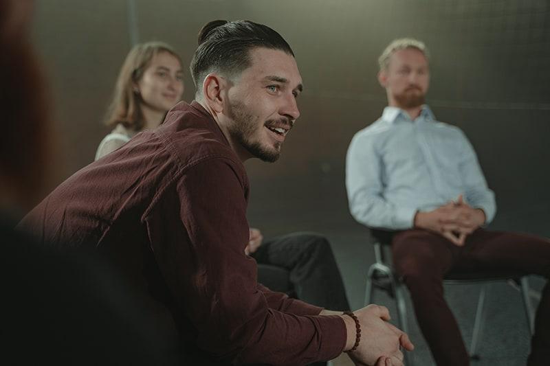 ein lächelnder Mann, der beiseite schaut, während er mit Familie sitzt