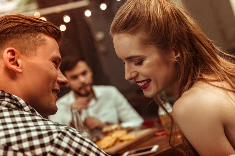 Ein lächelnder Mann und eine lächelnde Frau flirten, während sie mit Freunden im Restaurant sitzen