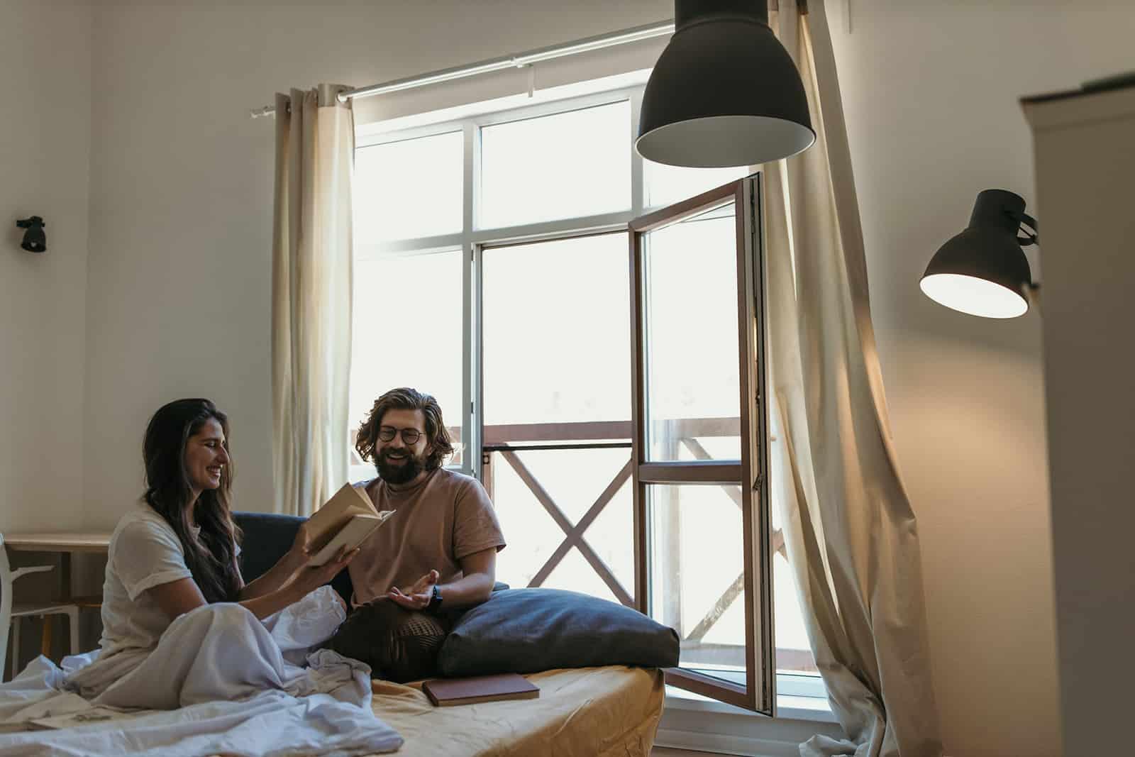 ein lachendes Paar sitzt auf dem Bett und liest ein Buch