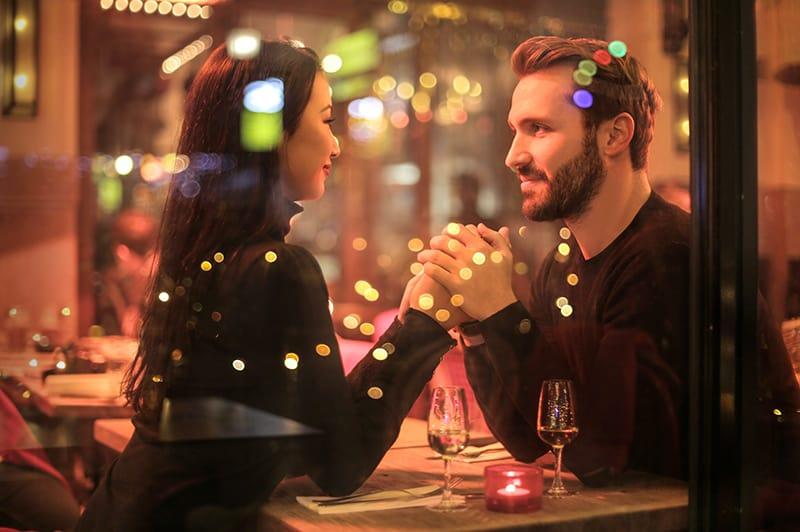 ein liebevolles Paar Händchen haltend in einem romantischen Restaurant sitzen