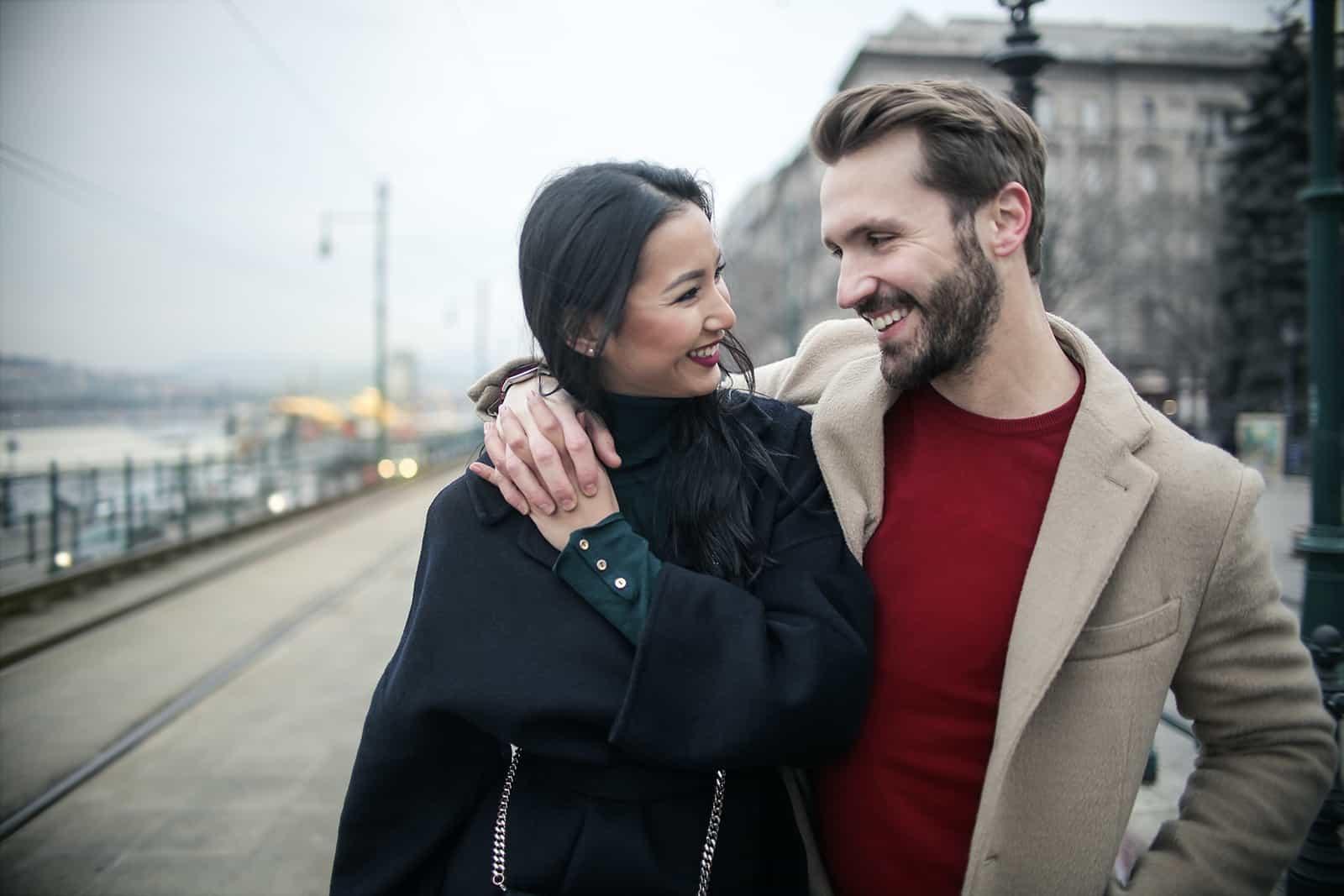 ein liebevolles Paar, das geht, sich umarmt und miteinander lächelt