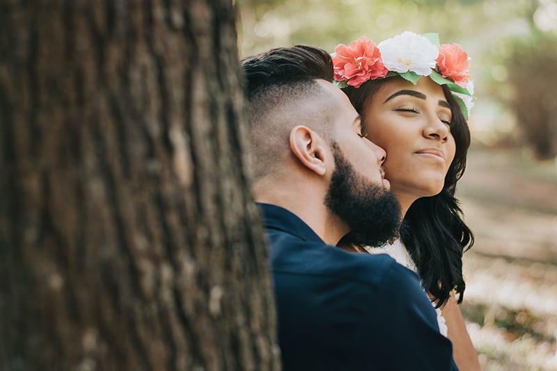 ein liebendes Paar, das kuschelt, während es in der Nähe des Baumes steht