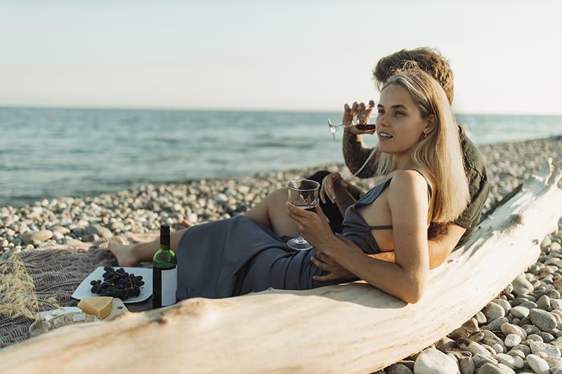 Ein liebevolles Paar sitzt am Strand und trinkt Wein