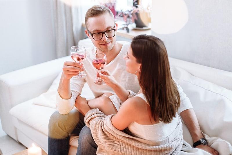 ein liebevolles Paar, das auf der Couch einen Toast mit Getränken macht