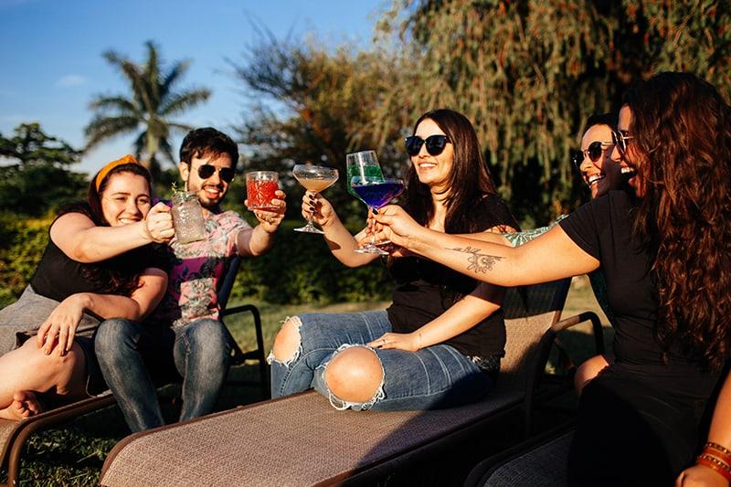 ein liebevolles Paar, das mit Freundinnen auf der Party im Freien anstößt
