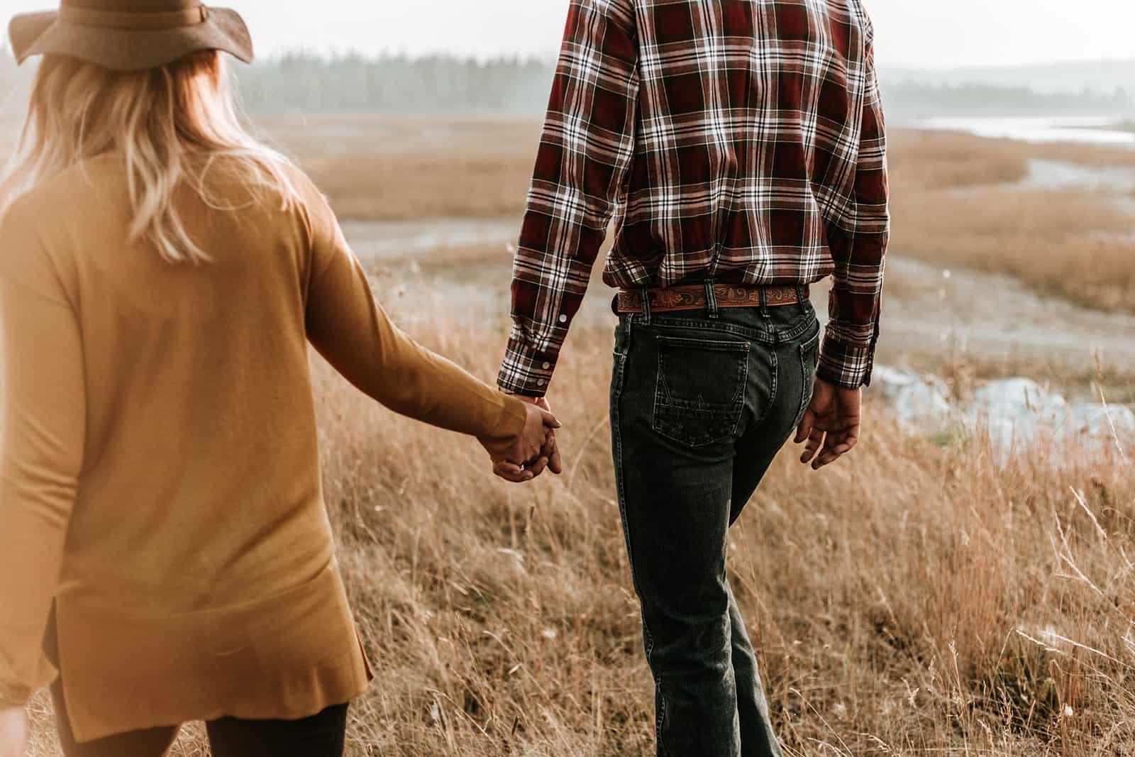 ein Paar Händchen haltend beim Gehen über das trockene Gras
