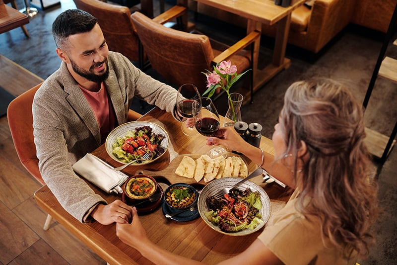 ein Paar Händchen haltend und einen Toast während eines Abendessens in einem Restaurant