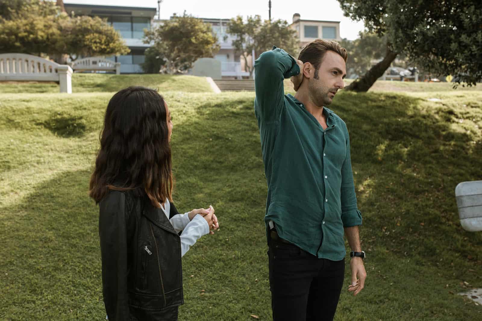 ein Paar, das im Gras steht und über ihre Beziehung spricht