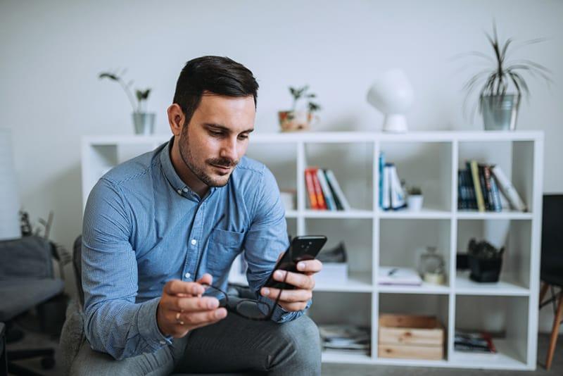 ein positiver Mann, der ein Smartphone benutzt, während er zu Hause sitzt