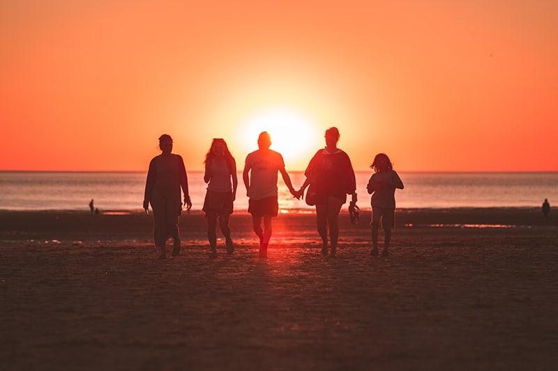 eine Familie, die während des Sonnenuntergangs am Strand spazieren geht