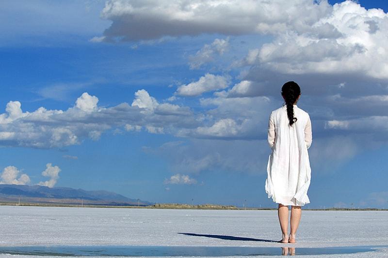 eine Frau, die am Strand steht und die Wolken betrachtet