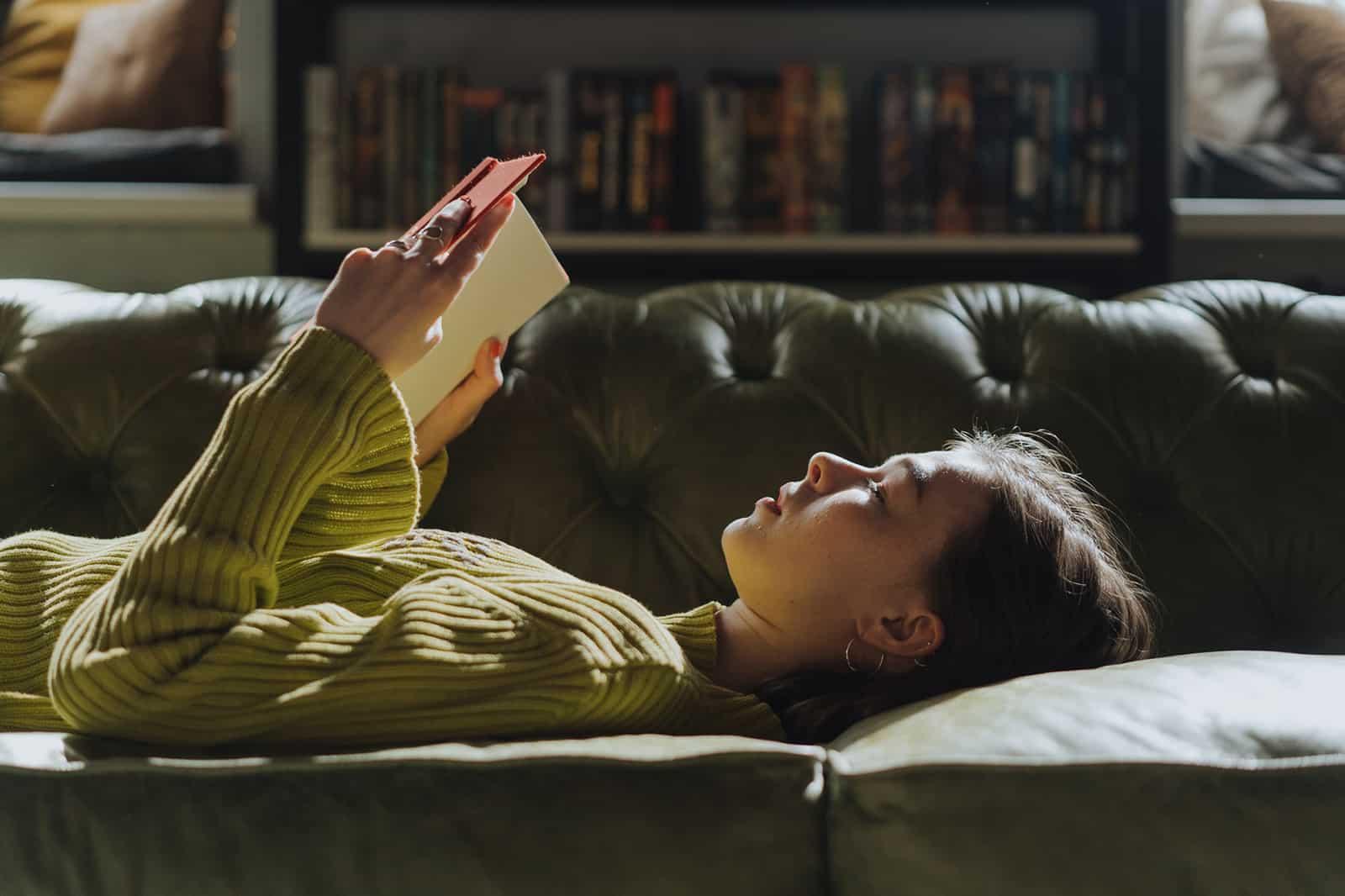 eine Frau, die auf der Couch liegt und ein Buch hält