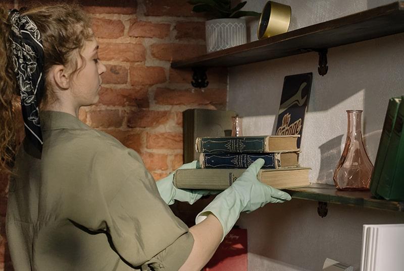 eine Frau, die Bücher in einem Regal organisiert, während sie den Raum putzt