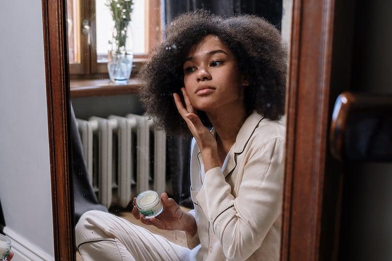eine Frau, die Creme auf ihr Gesicht aufträgt, während sie vor dem Spiegel sitzt