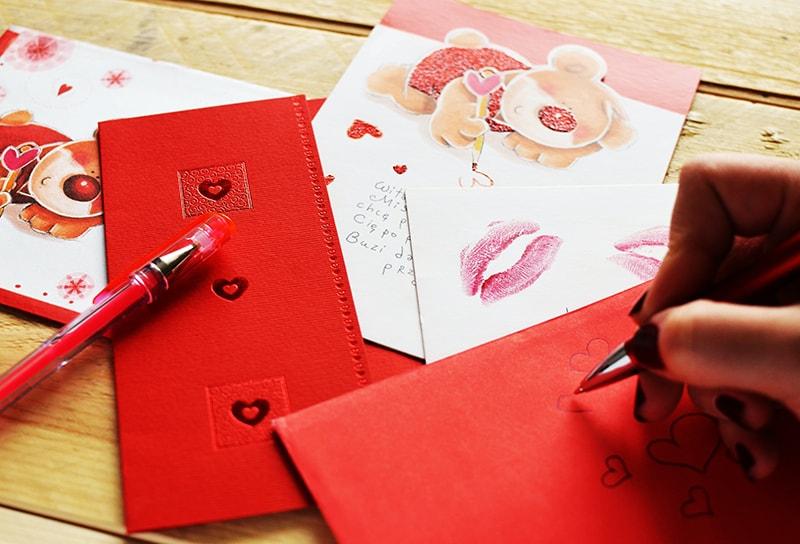 eine Frau, die Herzen auf rotem Papier mit einer Grußkarte daneben zeichnet
