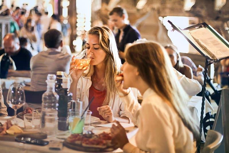 eine Frau, die Wein trinkt, während sie mit einer Freundin im Restaurant sitzt