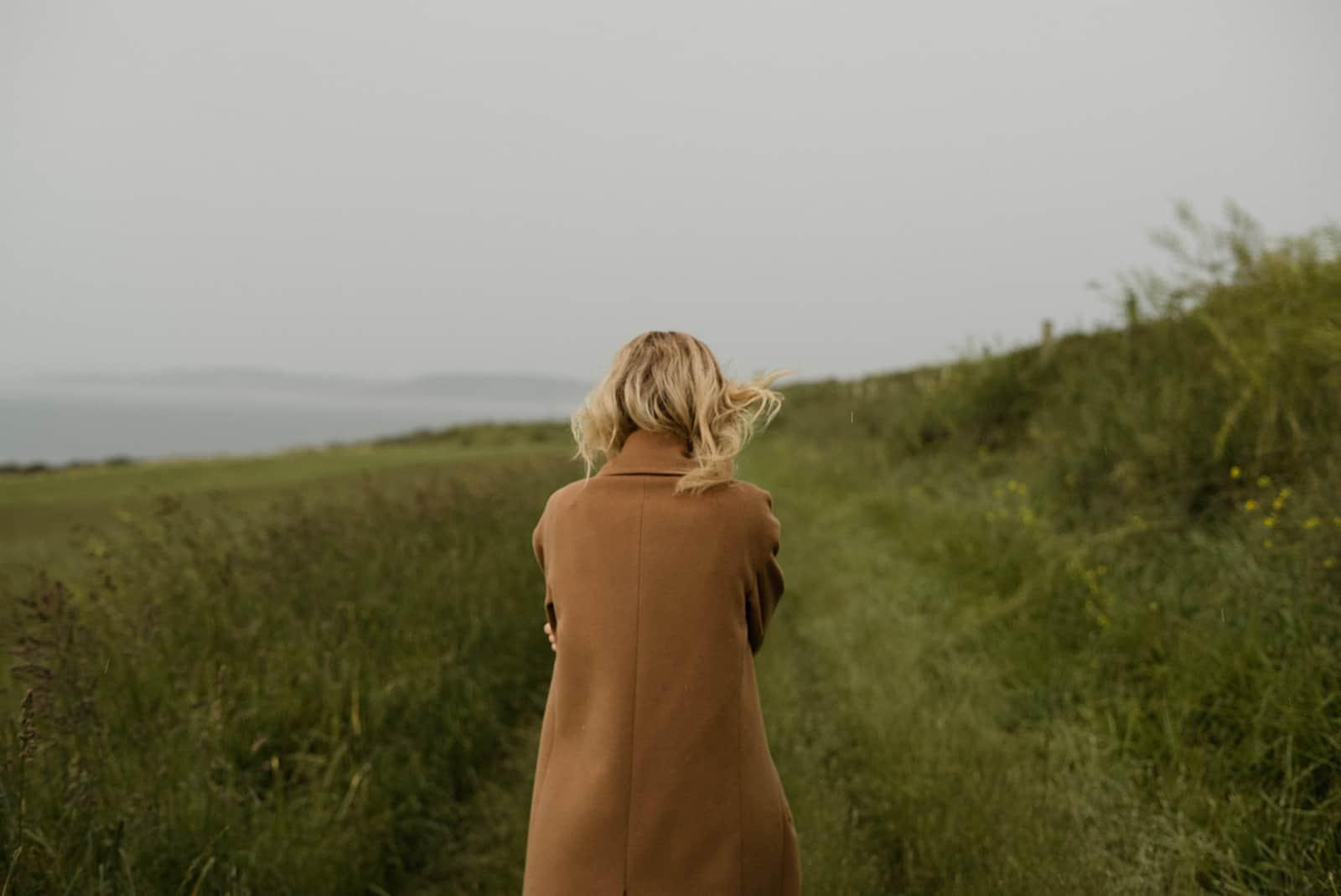 eine Frau, die an einem kalten Tag allein auf dem Feld geht
