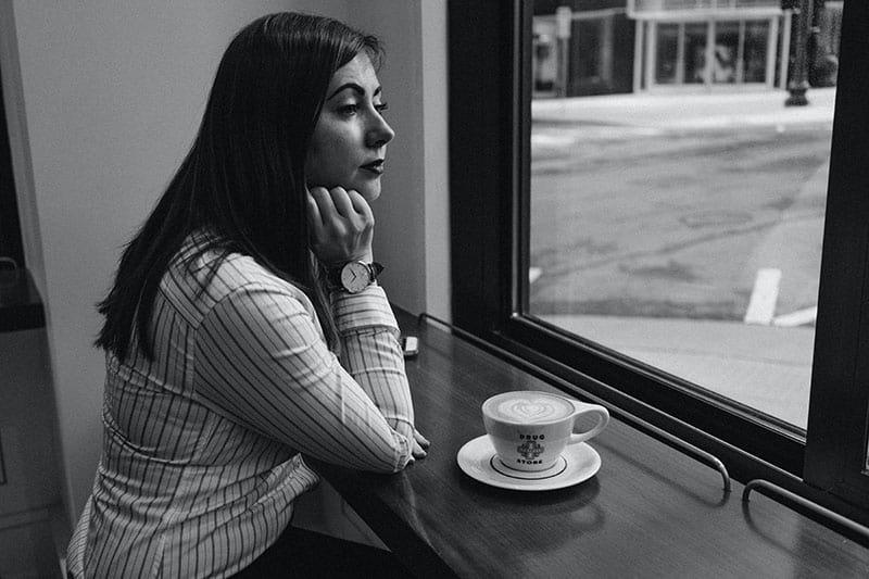 eine Frau, die alleine im Café am Fenster sitzt