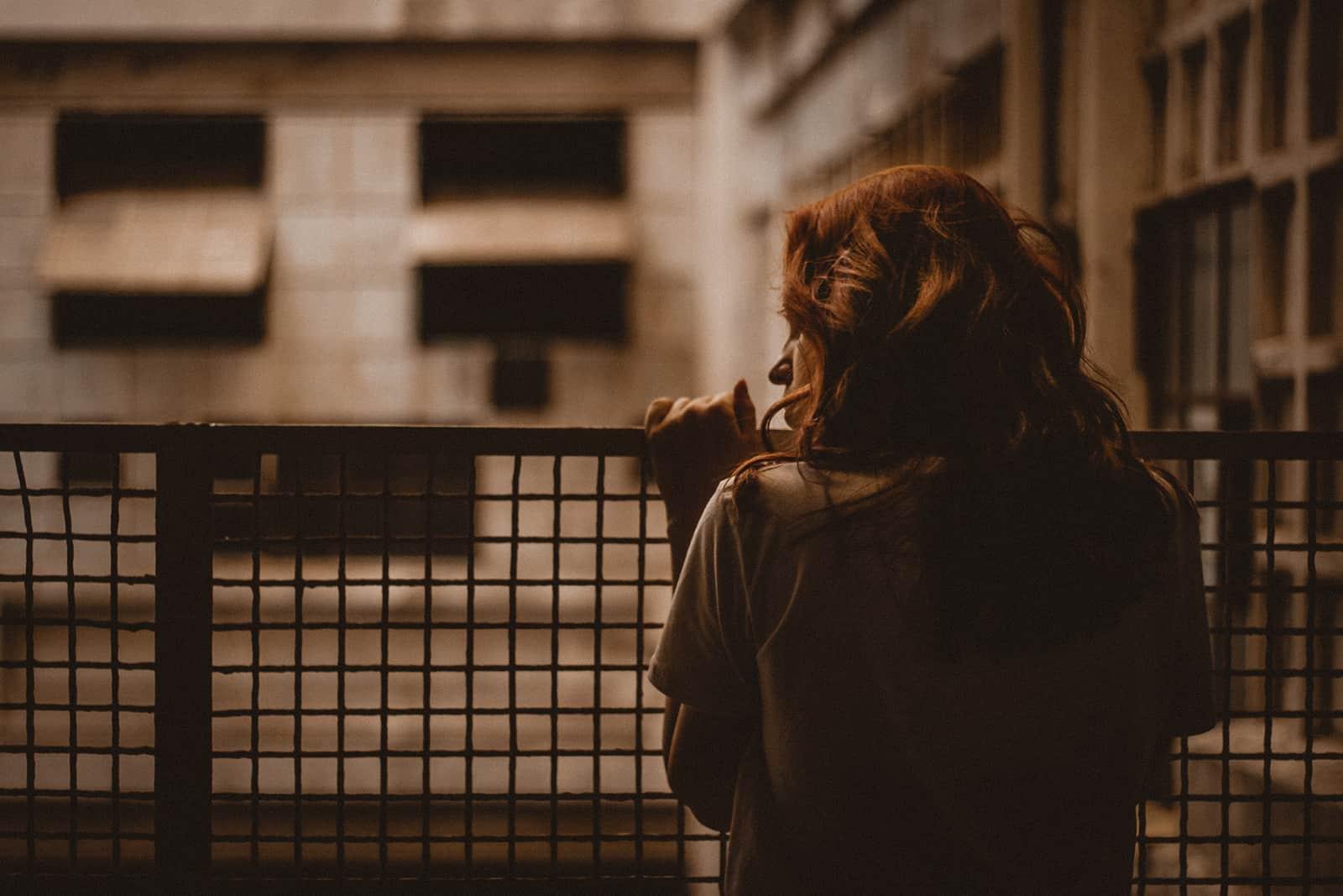 eine Frau, die sich am Geländer festhält und zur Seite schaut