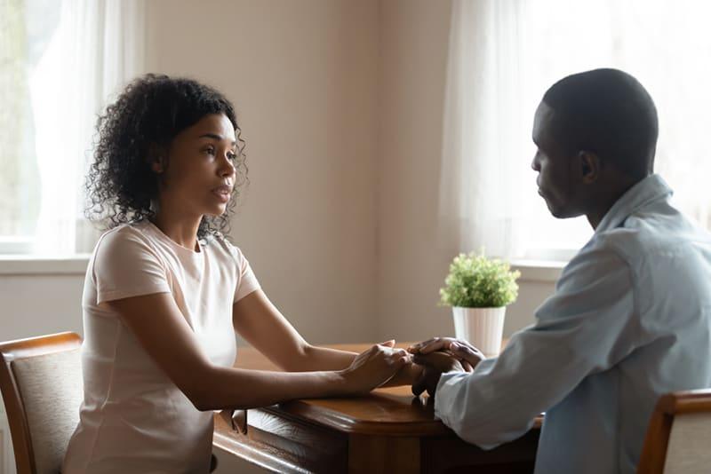 eine Frau, die die Hände ihres Freundes hält, während sie zu Hause spricht