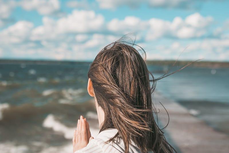 Eine Frau, die dankbar ist und sich ihren Handflächen anschließt, während sie auf den Ozean blickt