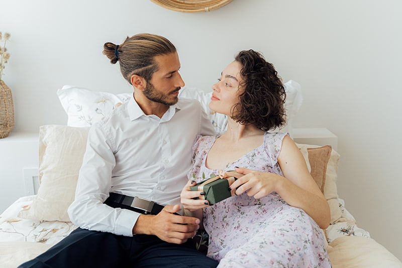 eine Frau, die eine Geschenkbox hält und ihren Partner ansieht, während sie zusammen auf dem Bett sitzt