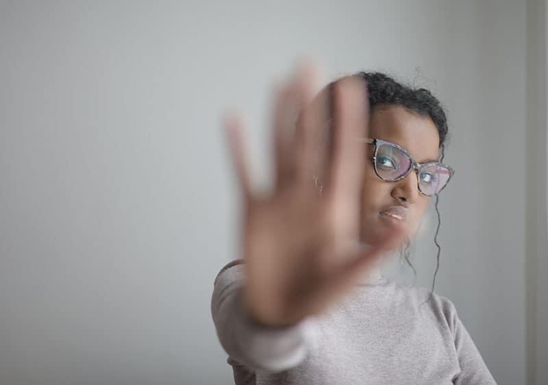 eine Frau, die mit ihrer Handfläche aufhört zu gestikulieren