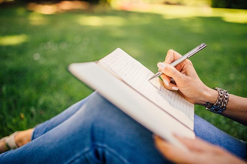 eine Frau, die einen Brief schreibt, während sie im Gras sitzt