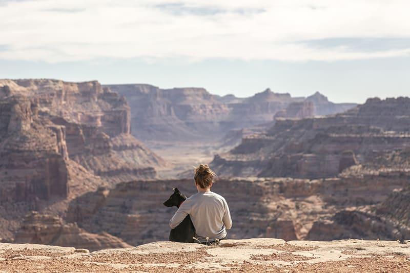 eine Frau, die einen Hund umarmt, während sie auf der Klippe sitzt